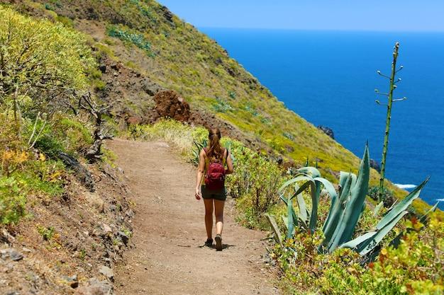 Mulher jovem alpinista caminhando em uma trilha com vista para o mar em tenerife