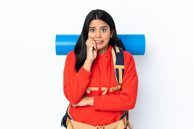 Mulher jovem alpinista colombiana com uma mochila grande isolada na parede branca, nervosa e assustada