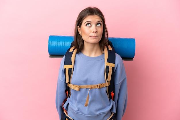 Mulher jovem alpinista com uma grande mochila isolada e olhando para cima