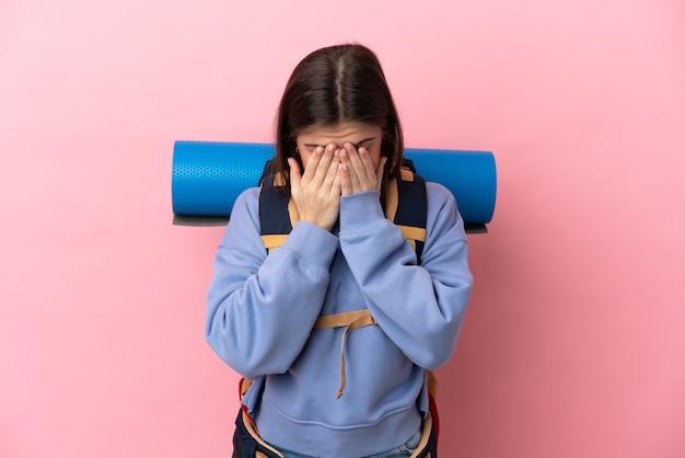 Mulher jovem alpinista com uma grande mochila isolada em um fundo rosa com expressão de cansaço e enjoo