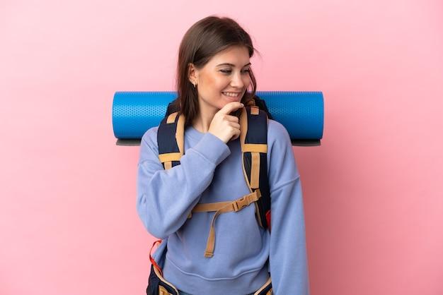 Mulher jovem alpinista com uma grande mochila isolada em um fundo rosa olhando para o lado e sorrindo