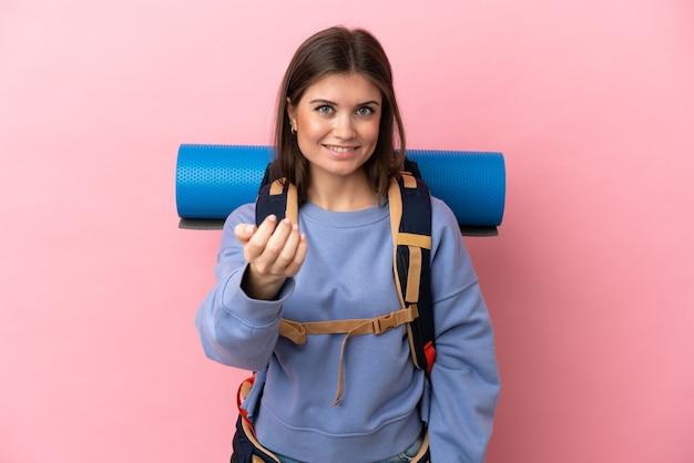 Mulher jovem alpinista com uma grande mochila isolada no fundo rosa, convidando a vir com a mão. feliz que você veio