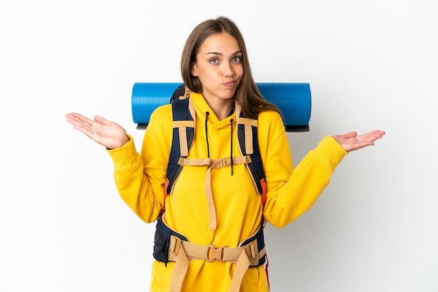 Mulher jovem alpinista com uma grande mochila isolada, tendo dúvidas ao levantar as mãos