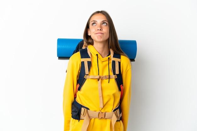 Mulher jovem alpinista com uma grande mochila sobre um fundo branco isolado e olhando para cima