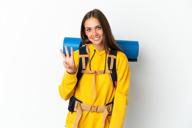 Mulher jovem alpinista com uma grande mochila sobre um fundo branco isolado feliz e contando três com os dedos