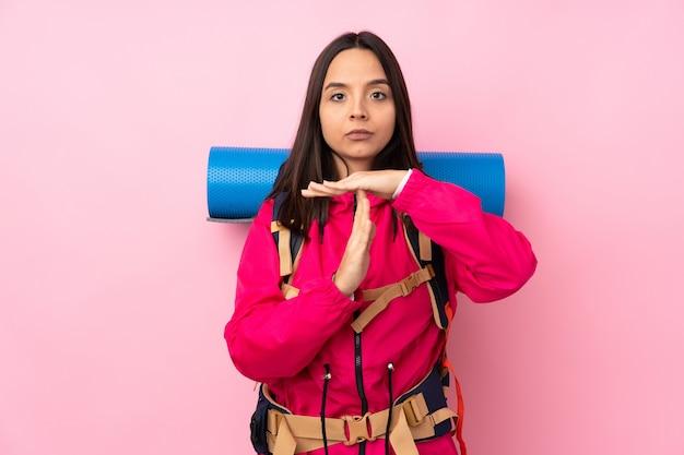 Mulher jovem alpinista com uma mochila grande, fazendo o gesto de tempo