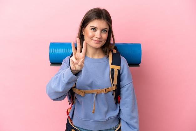 Mulher jovem alpinista com uma mochila grande isolada em um fundo rosa feliz e contando três com os dedos