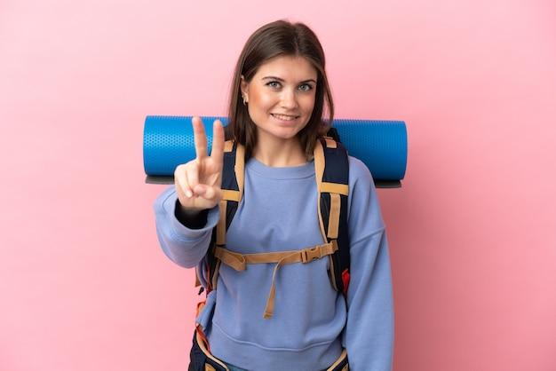 Mulher jovem alpinista com uma mochila grande isolada em um fundo rosa sorrindo e mostrando sinal de vitória