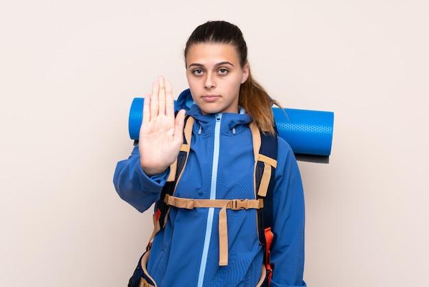 Mulher jovem alpinista com uma mochila grande sobre parede isolada, fazendo o gesto de parada com a mão