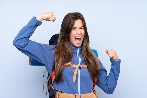 Mulher jovem alpinista com uma mochila grande sobre parede isolada