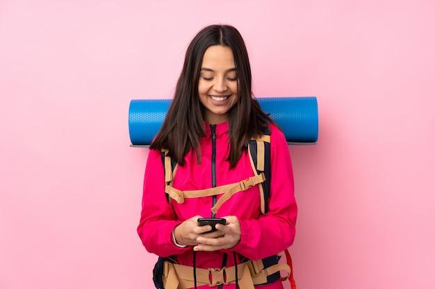 Mulher jovem alpinista com uma mochila grande sobre parede rosa isolada, enviando uma mensagem com o celular