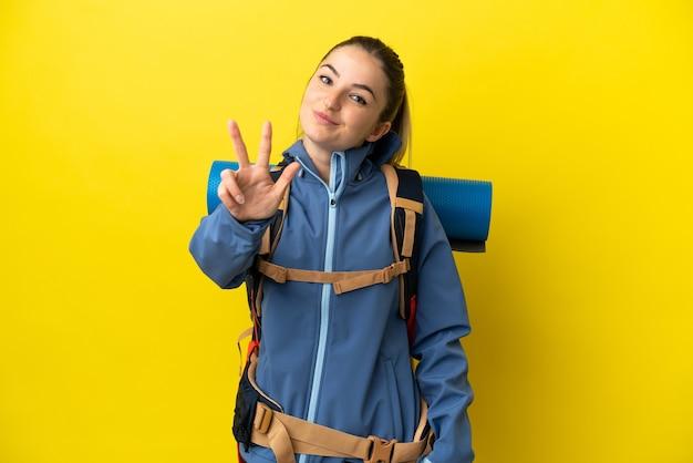 Mulher jovem alpinista com uma mochila grande sobre um fundo amarelo isolado feliz e contando três com os dedos