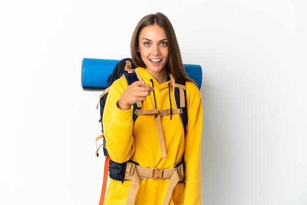 Mulher jovem alpinista com uma mochila grande sobre um fundo branco isolado surpresa e apontando para a frente