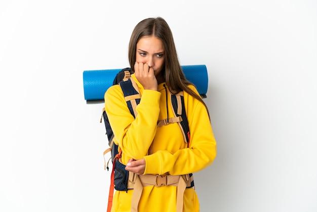 Mulher jovem alpinista com uma mochila grande sobre um fundo branco isolado, tendo dúvidas