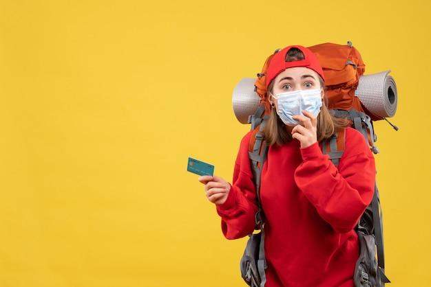 Mulher jovem alpinista de frente com mochila e máscara segurando um cartão de descontos