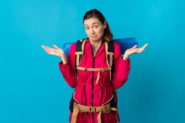 Mulher jovem alpinista sobre fundo azul isolado, tendo dúvidas ao levantar as mãos
