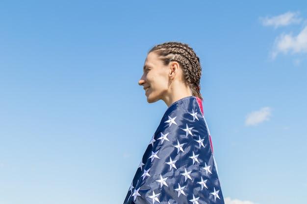 Mulher jovem americana feliz com afro-tranças envolto em listras e estrelas bandeira dos eua contra o céu azul.