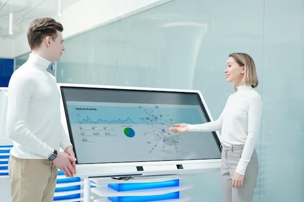 Mulher jovem amigável e positiva apontando para uma tela interativa e analisando estatísticas de distribuição de produtos com um colega