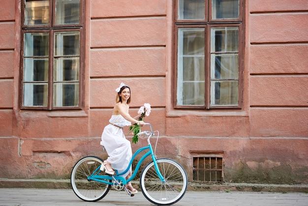 Mulher jovem andando de bicicleta azul ao ar livre