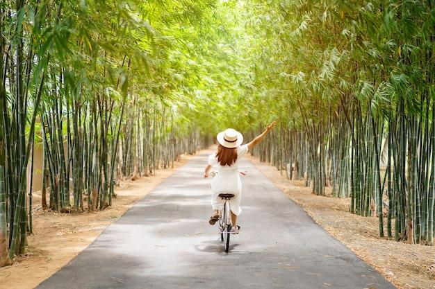 Mulher jovem andando de bicicleta em uma floresta de bambu