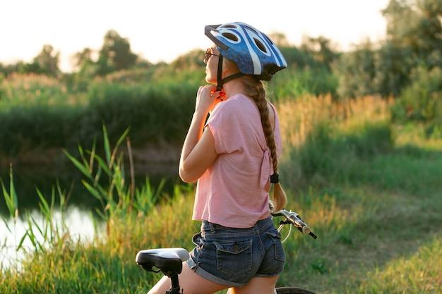 Mulher jovem andando de bicicleta no calçadão à beira do rio e prados inspirada na natureza cercada
