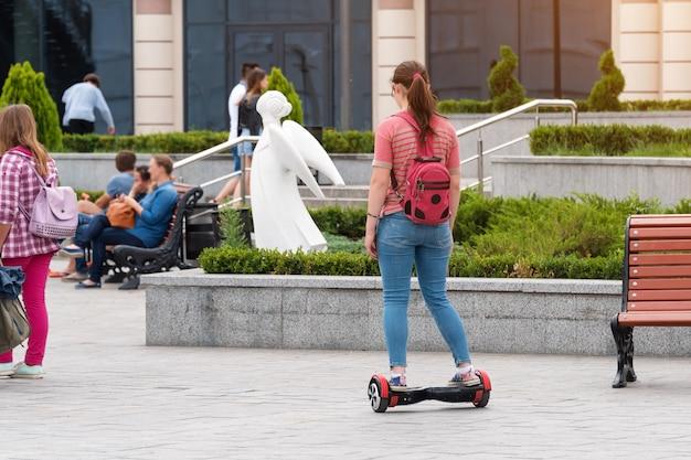 Mulher jovem andando de prancha na praça da cidade