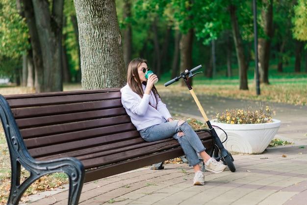 Mulher jovem andando de scooter no parque, sentada em um banco
