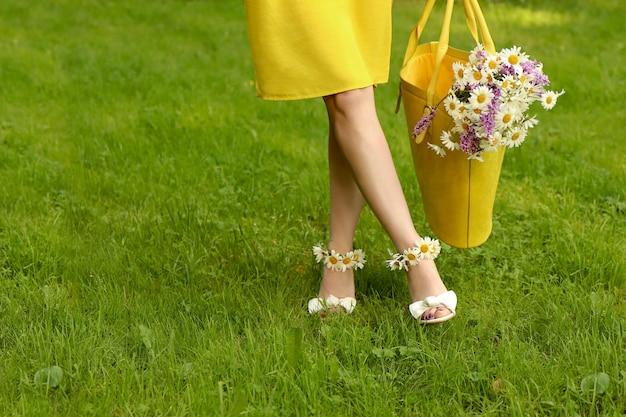 Mulher jovem andando em sandálias com margaridas nos pés e flores em uma bolsa amarela.