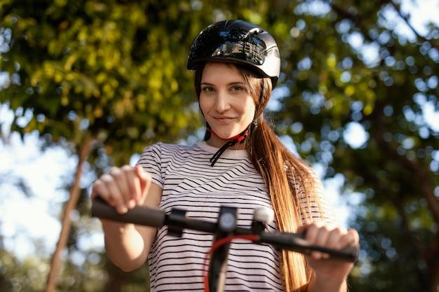 Mulher jovem andando em uma scooter elétrica em um parque