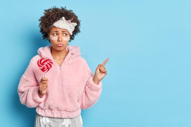 Mulher jovem angustiada com cabelo encaracolado indica acima no espaço em branco, vestida de pijama, segurando um doce em forma de coração, está com mau humor no início da manhã, isolado sobre a parede azul
