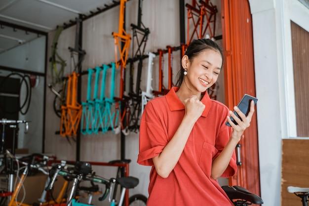Mulher jovem animada com as mãos cerradas ao olhar para a tela do smartphone