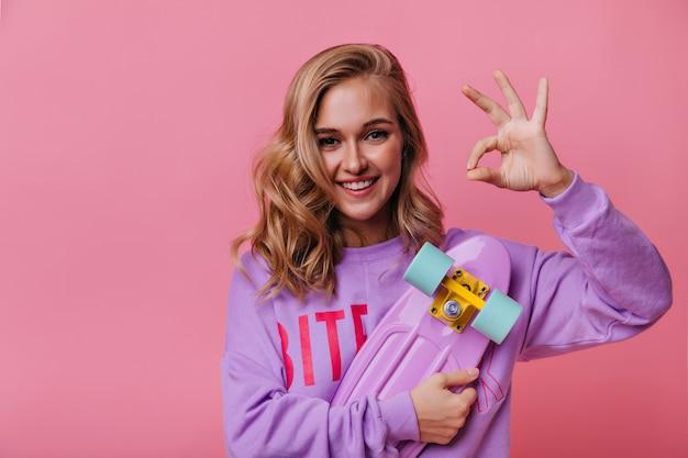 Mulher jovem animada com cabelo loiro ondulado, posando com o skate. menina sorridente relaxada na camisa roxa, mostrando sinal de tudo bem.