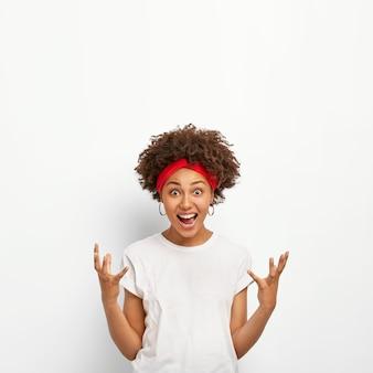 Mulher jovem animada com cabelos crespos encaracolados, gesticula ativamente, ri, sente emoções agradáveis ao ver algo legal e agradável