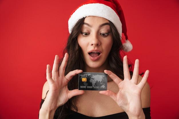Mulher jovem animada com um chapéu de natal em pé, isolada sobre o vermelho, mostrando um cartão de crédito de plástico