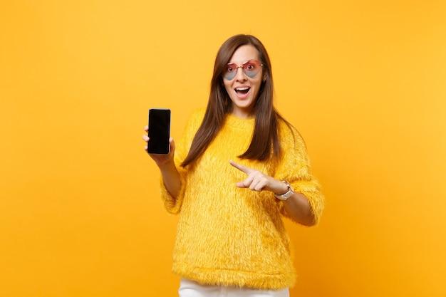 Mulher jovem animada em copos de coração apontando o dedo indicador no celular com tela vazia preta em branco, isolada em fundo amarelo brilhante. estilo de vida de emoções sinceras de pessoas. área de publicidade.