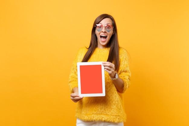 Mulher jovem animada em copos de coração de camisola, segurando o computador tablet pc com tela vazia preta em branco, isolada no fundo amarelo brilhante. conceito de estilo de vida de emoções sinceras de pessoas. área de publicidade.