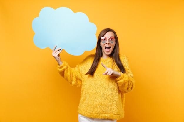 Mulher jovem animada em óculos de coração, apontando o dedo indicador no vazio azul em branco say nuvem, balão de fala isolado em fundo amarelo. emoções sinceras de pessoas, conceito de estilo de vida. área de publicidade.
