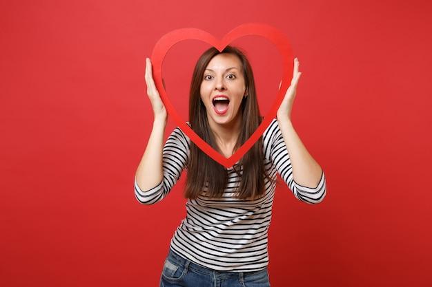 Mulher jovem animada, mantendo a boca bem aberta, parecendo surpreso e segurando um grande coração de madeira vermelho isolado no fundo da parede vermelha brilhante. emoções sinceras de pessoas, conceito de estilo de vida. simule o espaço da cópia.