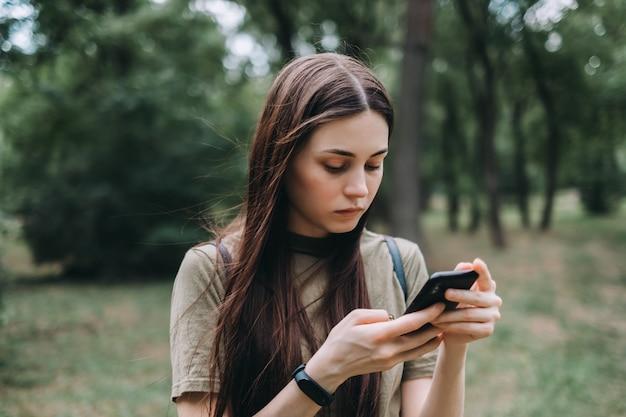 Mulher jovem animada no parque da cidade usando smartphone e digitar texto.