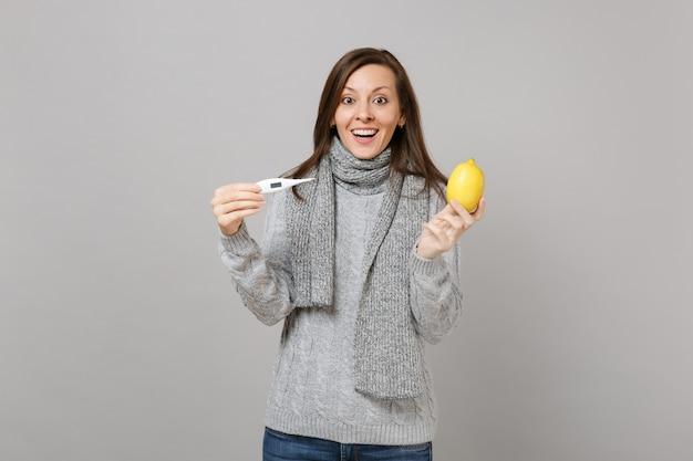 Mulher jovem animada no suéter cinza, lenço segurando termômetro de limão isolado no fundo da parede cinza no estúdio. estilo de vida saudável, tratamento de doença doente, conceito de estação fria. simule o espaço da cópia.