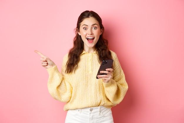 Mulher jovem animada segurando o celular apontando o dedo para o lado esquerdo da copyspace