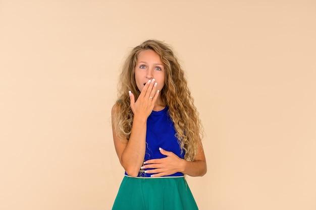 Mulher jovem animada surpresa, cobrindo a boca com a mão, sobre fundo bege isolado. Foto Premium