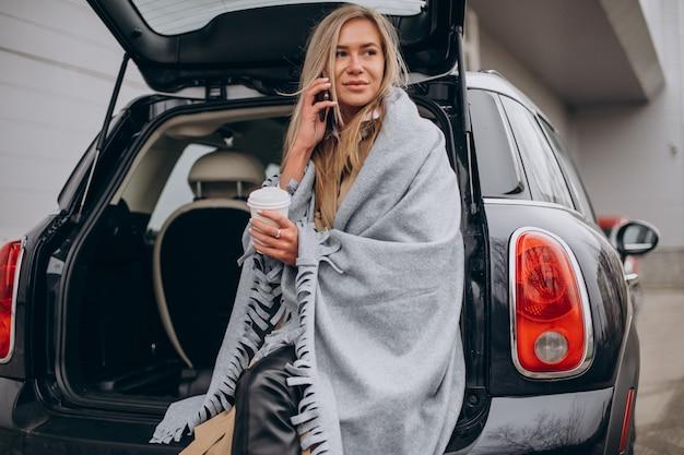 Mulher jovem ao lado do carro bebendo café