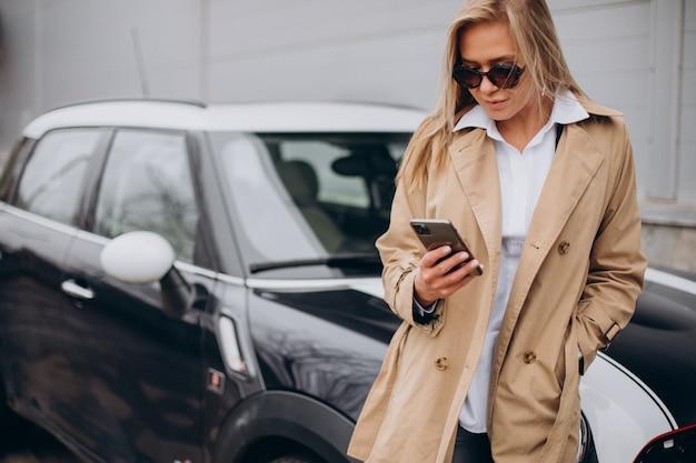 Mulher jovem ao lado do carro