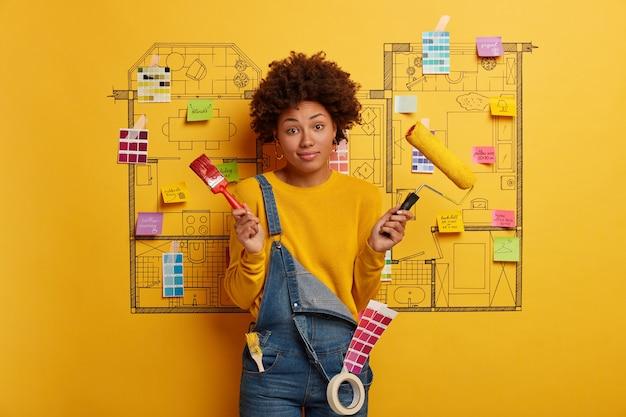Mulher jovem ao lado do esboço do projeto da casa, pronto para reforma Foto gratuita