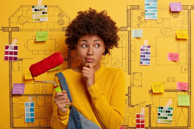Mulher jovem ao lado do esboço do projeto da casa, pronto para reforma