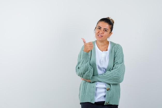 Mulher jovem aparecendo o polegar enquanto segura a mão no cotovelo em uma camiseta branca e um casaco de lã verde menta e olhando séria
