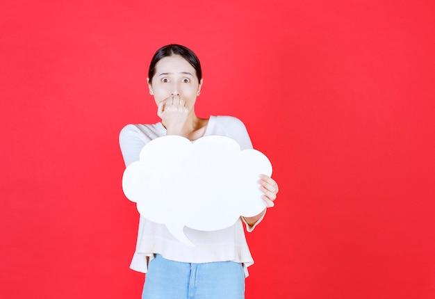 Mulher jovem apavorada segurando um quadro de ideias e levando a mão à boca