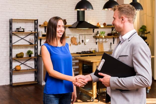 Mulher jovem, apertando mão, com, um, homem negócios