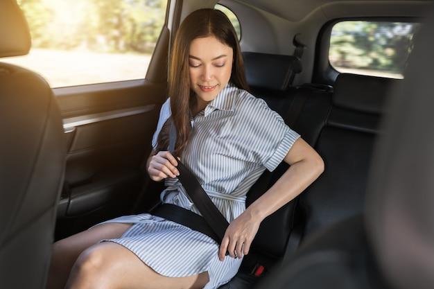 Mulher jovem apertando o cinto de segurança enquanto está sentada no banco de trás do carro